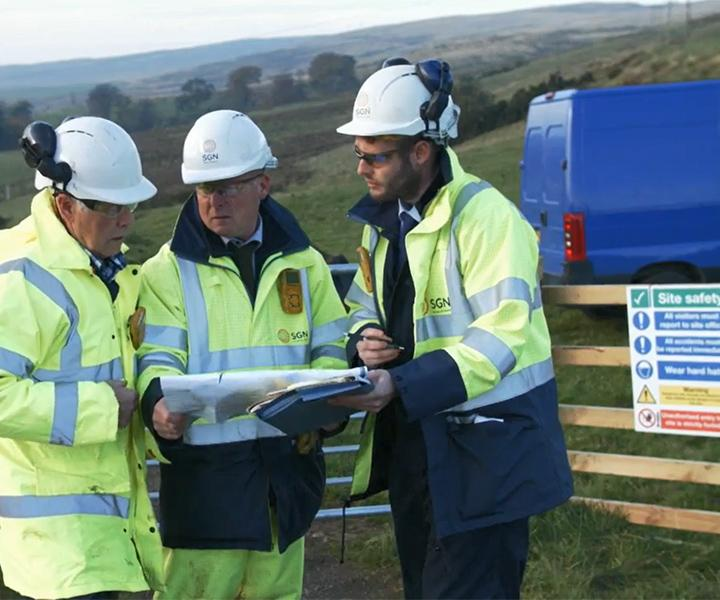 SGN colleagues standing with a customer in a field and are looking at a map.  The three people are wearing high-viz jackets and hard hats.